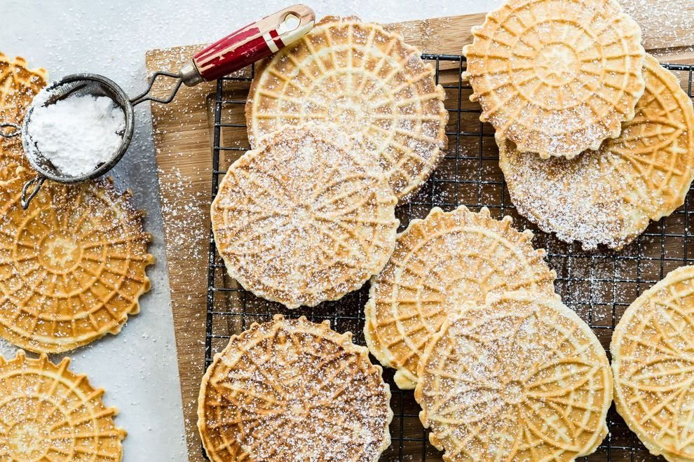 Pizzelle on a cooling rack being dusted with powdered sugar.