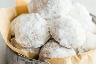 Mexican wedding cookies in a sliver tin on parchment paper.
