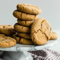 A stack of molasses cookies on a black and white cake platter.