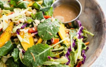 An easy recipe for Rainbow Thai Salad. It's full of colorful vegetables, herbs, sweet mango, crunchy nuts, and a delicious sweet and spicy Peanut Dressing!