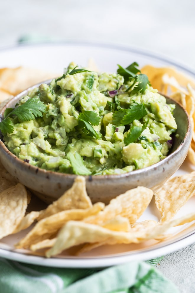 Chipotle guacamole in a brown dish on a white platter with tortilla chips.