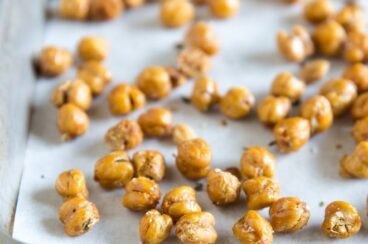 A side shot of roasted chickpeas on a baking sheet with parchment paper.