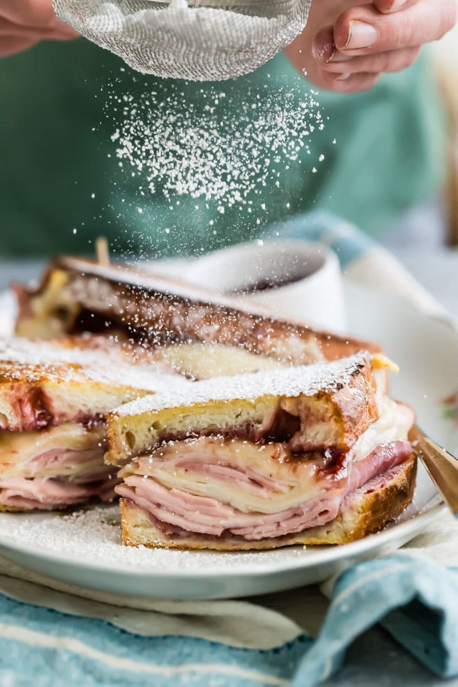 An easy Monte Cristo Sandwich recipe layered with ham, turkey, and Swiss, then battered and fried in the oven. Dust with powdered sugar for the ultimate breakfast sandwich!
