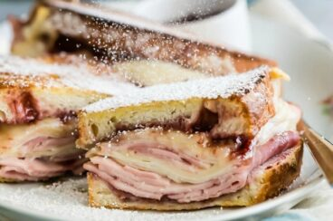 A monte cristo sandwich on a white platter being dusted with powdered sugar.