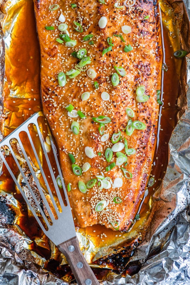 Sweet, salty, spicy, sticky, umami. This Asian Salmon in foil is a fool-proof recipe to get dinner on the table fast with the least amount of effort! Wrapping the salmon in foil seals in all the flavor and ensures a tender, flaky texture, while the last two minutes of broiling gives your salmon an irresistible glaze. All you have to do is toss the foil at the end .. no cleanup required.