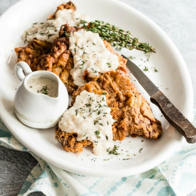 An easy recipe for Chicken Fried Steak. Battered in buttermilk, fried until crispy brown and smothered in a delicious, creamy homemade gravy.