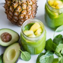Pineapple paradise spinach smoothie in a clear mason jar.