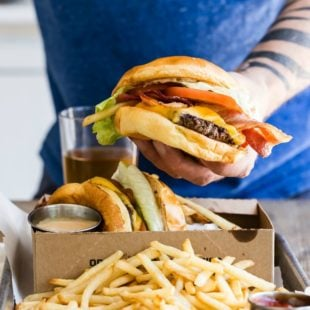 Someone holding a bacon cheeseburger over a box with a side of fries.