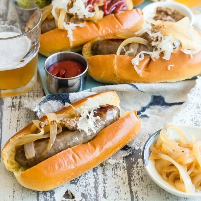 Beer brats topped with onions and shredded cheese.