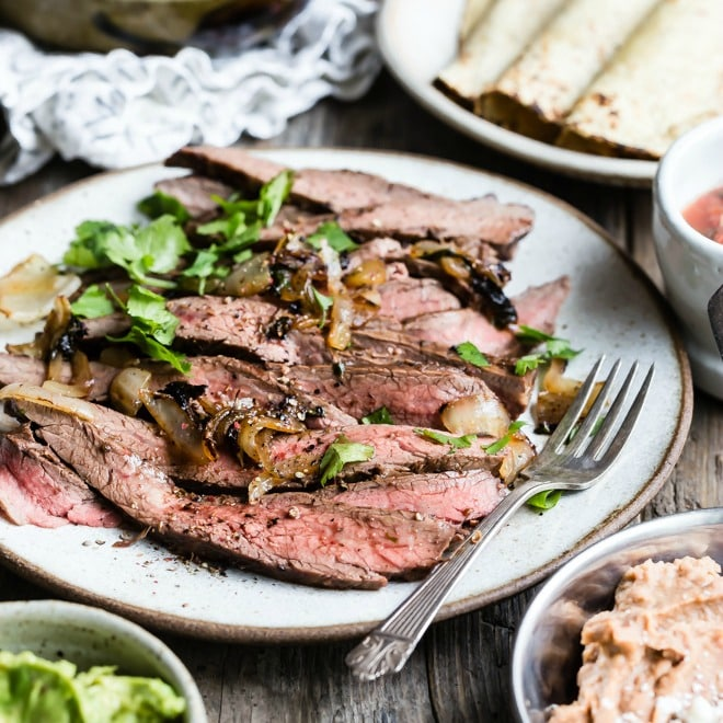 Carne asada on a white plate with a silver fork.