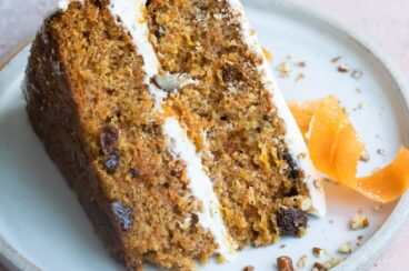 A slice of carrot cake on a blue plate with a candied carrot peel.