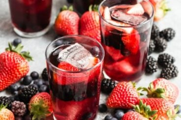 Iced tea berry sangria in two clear glasses surrounded by berries.
