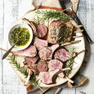 Roast rack of lamb on a white platter.