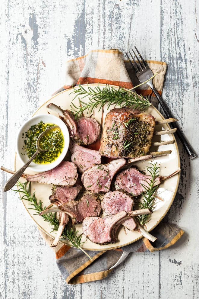 A rack of lamb on a gray plate.