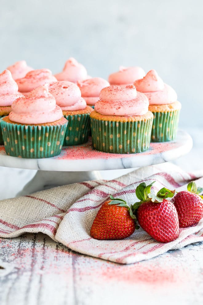 A cake plate with strawberry cupcakes on it.