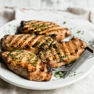 Succulent grilled pork chops make a perfect dinner, any night of the week. A super simple marinade that you throw together with common pantry ingredients does all the work for you; all you have to do is fire up the grill and make a salad.