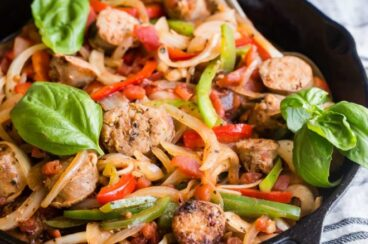 Italian sausage and peppers in a black cast iron skillet.