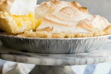 A lemon meringue pie with a piece being lifted out.