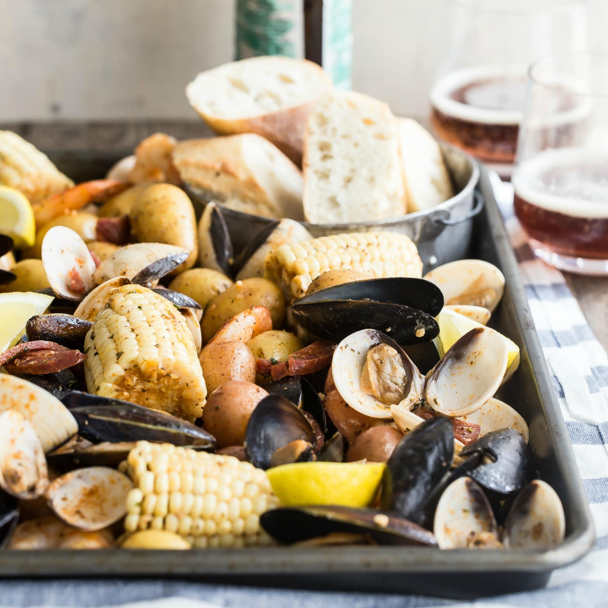 If you can't find your way to a beach this summer, you can make the beach come to you with this sheet pan clam bake, loaded with fresh shrimp, littleneck clams, potatoes, chorizo, and corn. Even better, it all bakes up in one pan for minimal cleanup. Spread a blanket out in the backyard—it's time for a clam bake!