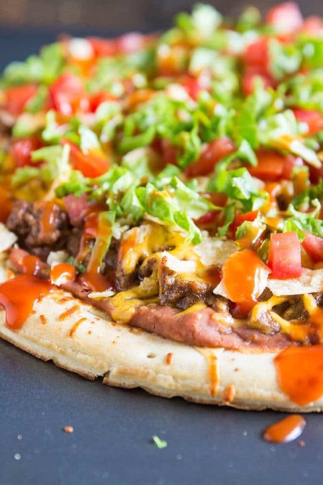 An easy recipe for Taco Pizza. Start with a store-bought crust and top with a salsa-refried beans mix, seasoned ground beef, cheese, and crunchy tortilla chips. Bake until bubbly and then top with lettuce, tomatoes, and your favorite taco sauce! Ready in 30 minutes or less and so delicious.