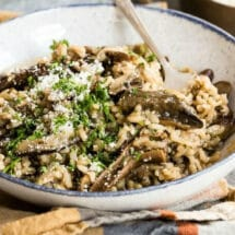 Mushroom risotto in a white bowl.