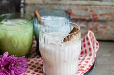 Agua de Horchata in three glasses on a sliver serving tray lined with a checkered towel.