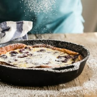 Cherry clafoutis in a black cast iron skillet being sprinkled with powdered sugar.