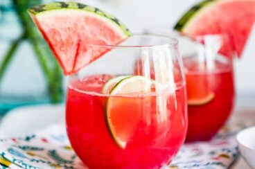 Watermelon agua fresca in glasses with wedges of watermelon.