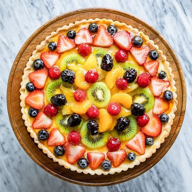 An overhead shot of fresh fruit tart on a wooden stand.