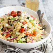 Greek pasta salad in a white serving bowl.