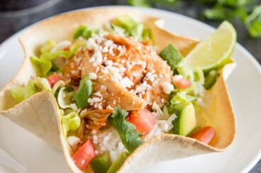This Chicken Tortilla Bowl recipe makes dinner so easy! Made with slow cooker salsa chicken, rice, and all your favorite toppings, it's fast, fresh, and so delicious! Or, leave out the rice for an easy entree salad for lunch or dinner. Everything can be prepped ahead so dinner is ready in minutes.
