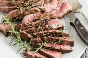 Grilled london broil slices on a white serving plate.