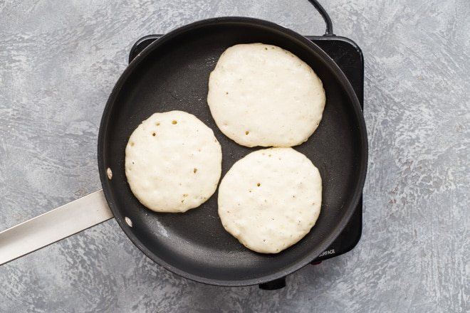 3 pancakes cooking in a skillet.