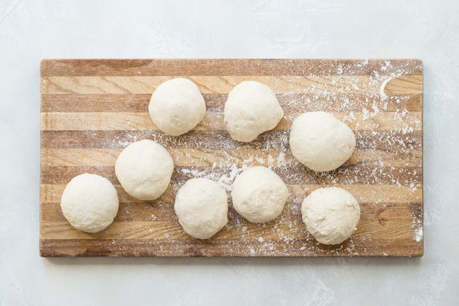 Picture of eight pizza dough balls on a cutting board.