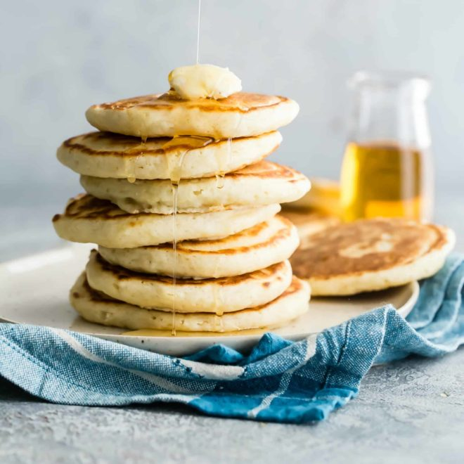 Pancakes in a stack with syrup drizzled on top.