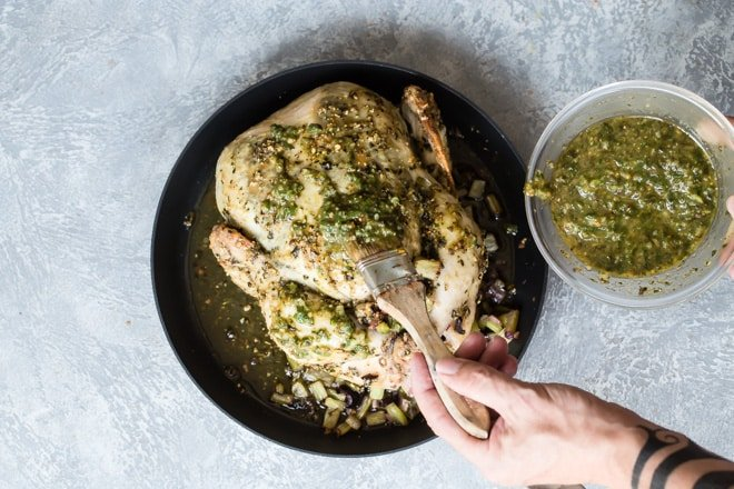 This recipe for Pesto Roasted Chicken uses a homemade pesto rubbed under the skin to give the chicken unbelievable flavor as it cooks. This is a perfect way to enjoy the end of summer's fresh basil, and get you out of that grocery store rotisserie chicken rut.