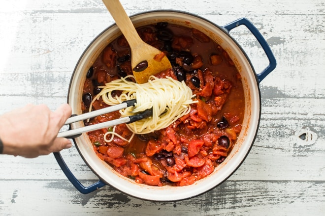 Spaghetti alla Puttanesca: leave it to the Italians to craft a magical dinner out of a little bit of this, and a little bit of that. Garlic, olives, anchovies, tomatoes, and chili pepper come together in this lightning fast recipe that takes eating well to a new level.