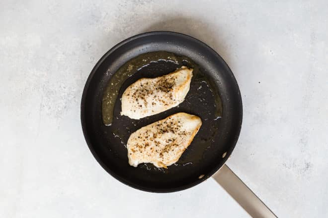 Chicken breast cooking in a skillet.