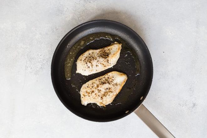 Chicken breasts being cooked in a pan.