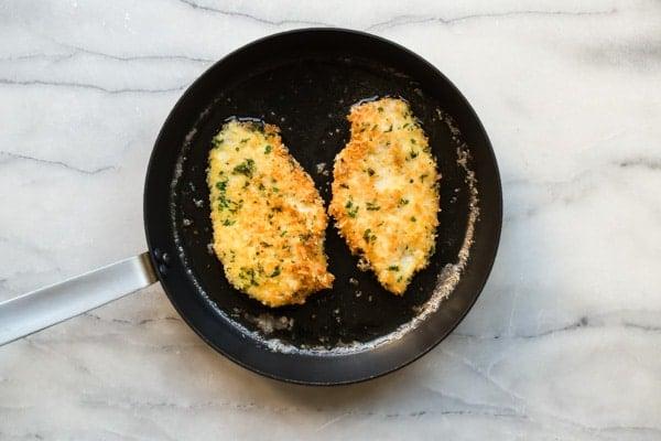 Breaded chicken cutlets frying in a pan.