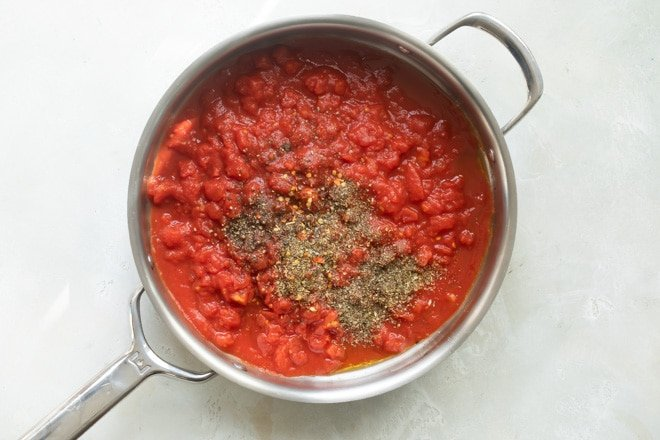 Marinara sauce cooking in a saucepan for chicken parmesan.