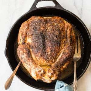 An overhead shot of how to make rotisserie chicken in a cast iron skillet.