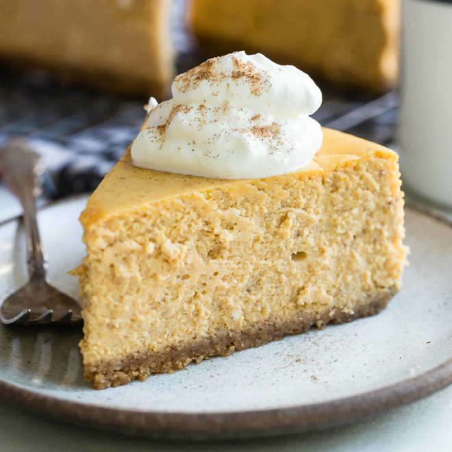 A slice of pumpkin cheesecake on a white plate with a silver fork.