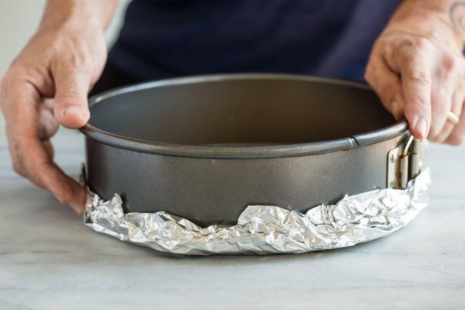 A spring form pan wrapped in foil on the bottom.