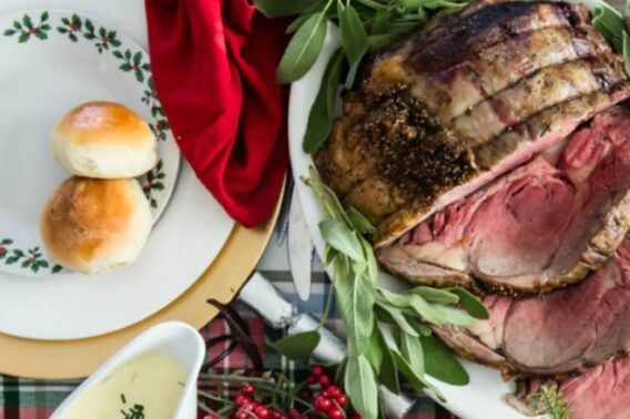 Prime rib with mustard creme sauce and homemade rolls on a festively decorated table.
