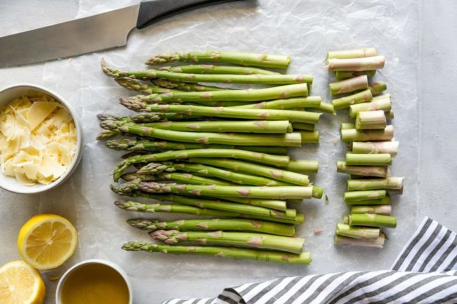 A simple method for roasting asparagus in the oven. The garlic adds an aromatic flavor, while the higher oven temperature cooks the asparagus quicker, meaning you will be able to enjoy your veggies sooner rather than later. The asparagus is so good for you, a shaving of Parmesan or any of your favorite cheese is definitely required!