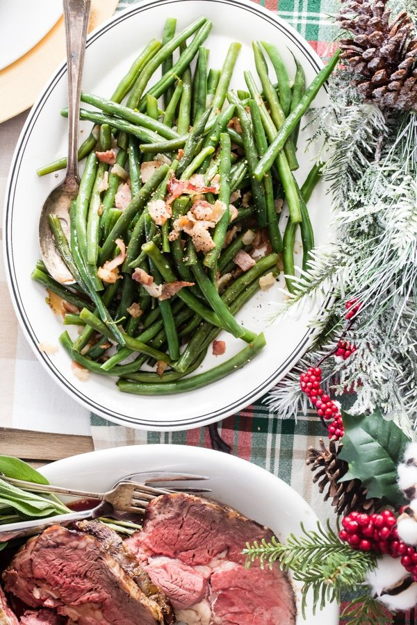 This recipe for Green Beans with Bacon has many names: Texas Roadhouse Green Beans, Southern Style Green Beans, or Arkansas Green Beans, to name just a few. I make mine with fresh green beans and just the right amount of brown sugar for a little extra flavor.