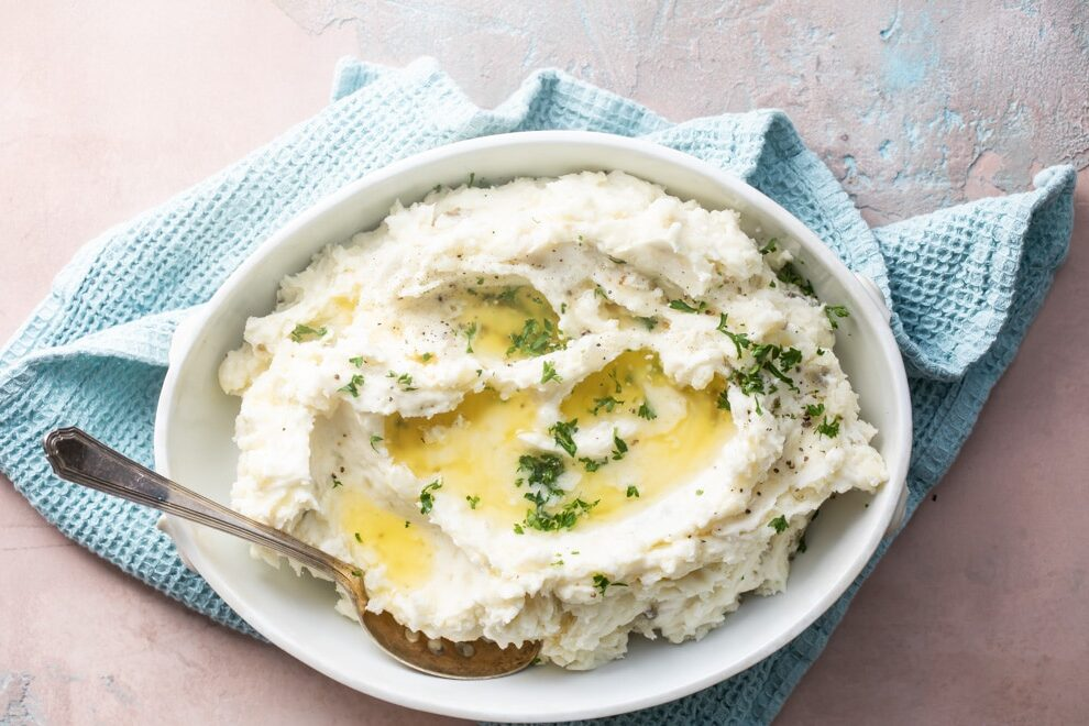Make ahead mashed potatoes with melted butter in a white serving dish with a spoon on a blue towel.