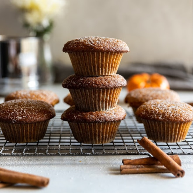 Pumpkin muffins stacked on a cooling rack.