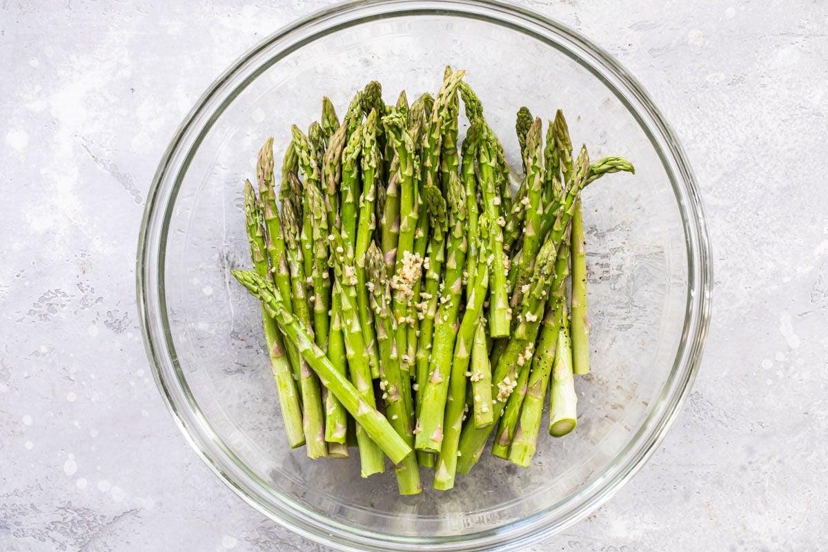 Raw asparagus in a bowl with garlic.